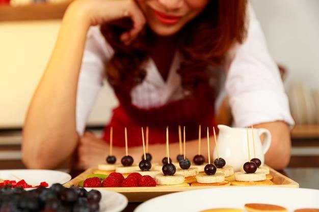주부는 막대기로 장식된 맛있는 맛있고 건강한 작은 혼합 과일 바나나 딸기 블루베리와 체리 팬케이크 전채 스택을 준비하고 장식합니다.