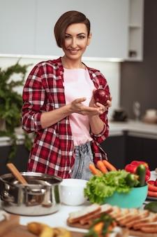 Домохозяйка готовит ужин для семьи, выбирая овощи, держа в руках красный лук