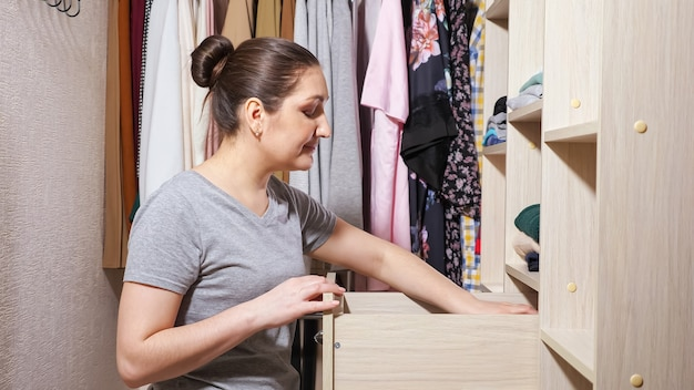 Housewife puts folded clean clothes into cabinet wooden drawer in contemporary light walkin closet