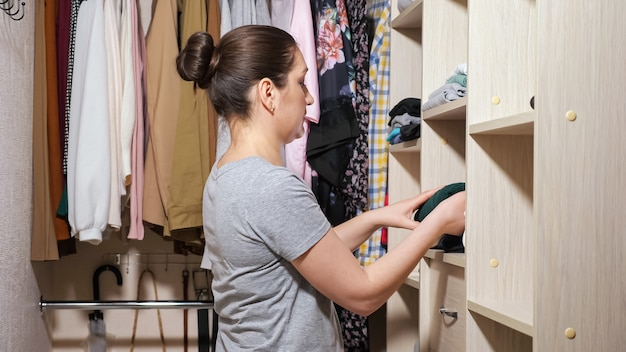 Housewife puts folded clean clothes on wooden shelves
