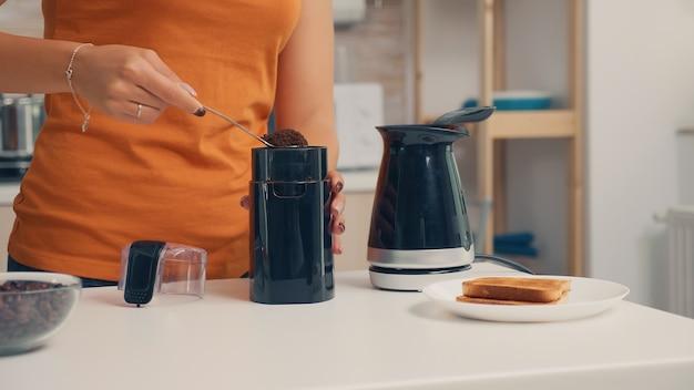 朝食時に電気ポットにコーヒーを入れる主婦。自宅で主婦が朝食、飲酒、仕事に行く前にコーヒーエスプレッソを挽くためにキッチンで挽きたてのコーヒーを作る