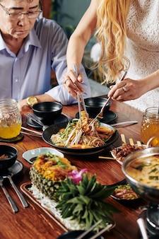 Домохозяйка кладет блюдо из миски в тарелку