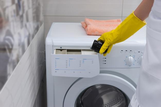 手袋をはめた手で柔軟仕上げ剤または洗剤を洗濯機に入れる主婦、クローズアップビュー
