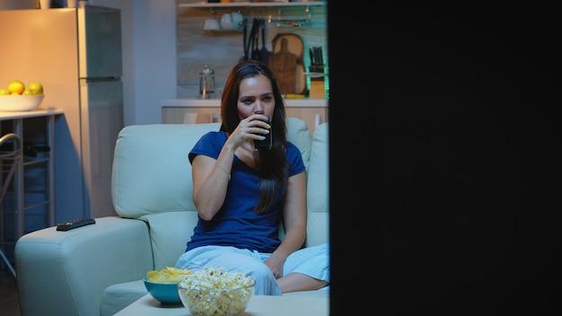 ポップコーンを食べたりジュースを飲んだりするコメディショーでリラックスする主婦。パジャマを着た快適なソファに座って自宅でテレビシリーズを見て夜を楽しんでいる興奮した面白がって家の一人の女性。