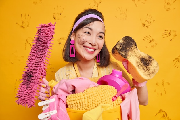 Housewife remains beautiful even during house cleaning has happy dreamy expression wears headband earrings poses with dirty sponge mop stands near basket full of laundry isolated on yellow