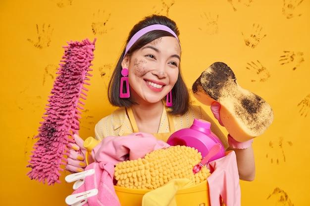 주부는 집안을 청소하는 동안에도 아름답습니다. 꿈꾸는 표정이 머리띠 귀걸이를 착용하고 더러운 스폰지 걸레 스탠드가 노란색에 고립 된 세탁물로 가득 찬 바구니 근처에 서 있습니다.