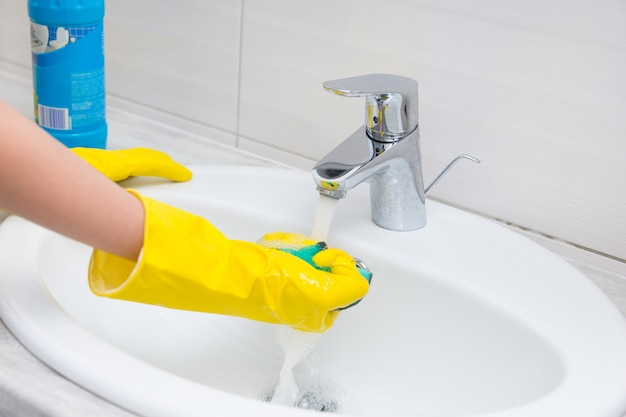 Housewife rinsing off a sponge for cleaning the bathroom under the running water from the hand basin, close up view of her gloved hands