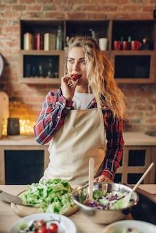 Домохозяйка сидит на столе и держит в руке помидор