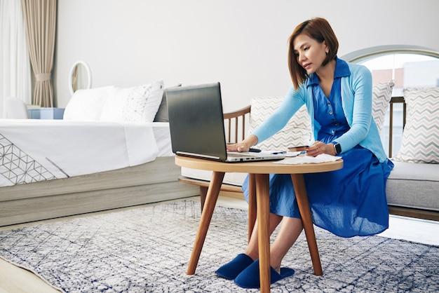 Домохозяйка сидит за столом в спальне и оплачивает счета онлайн с помощью кредитной карты