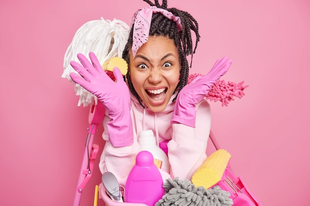 Housewife spreads palms screams very loudly has much housework being annoyed with naughty children who made mess in room wears rubber gloves uses cleaning supplies does family chores