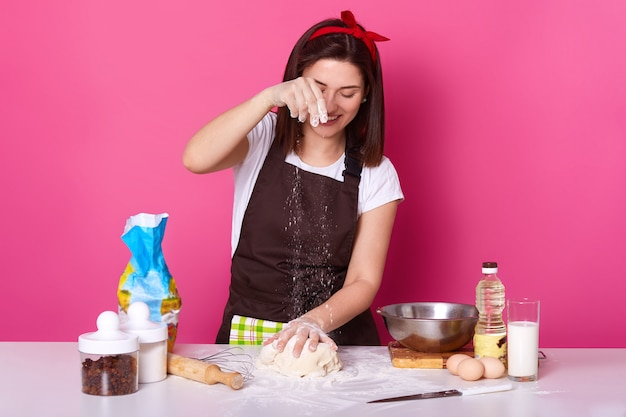 Housewife sprinkling flour over dough, cooking homemade pastry, baking easter cake, woman wearing brown apron, white t shirt, red hair band. cooking, preparing for holiday concept.