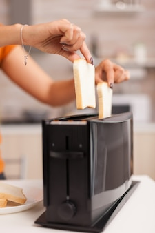 キッチンでおいしい朝食のためにパンのスライスを乾杯する主婦。