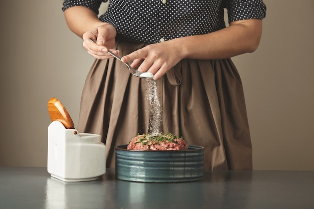 Housewife unrecognizable woman adds some salt in minced meat in ceramic bowl on blue table