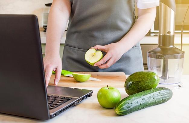 主婦はラップトップを使用し、スムージーのために新鮮な果物や野菜を準備します。
