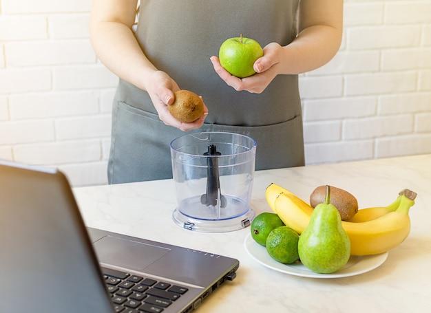 主婦はラップトップを使用し、新鮮なフルーツスムージーを準備します。