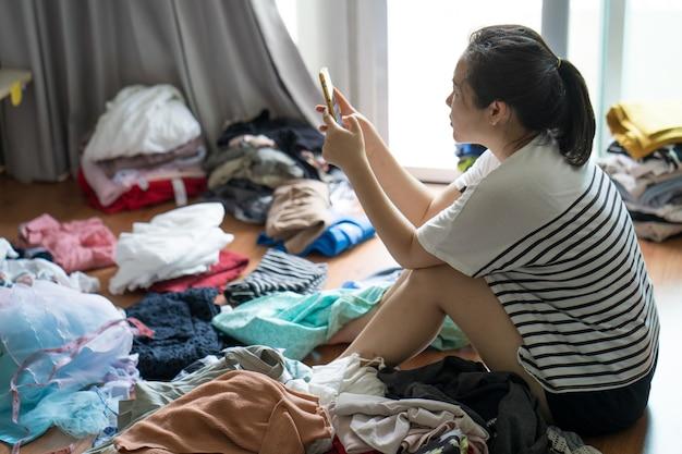 服を折りたたんで携帯電話を使う主婦