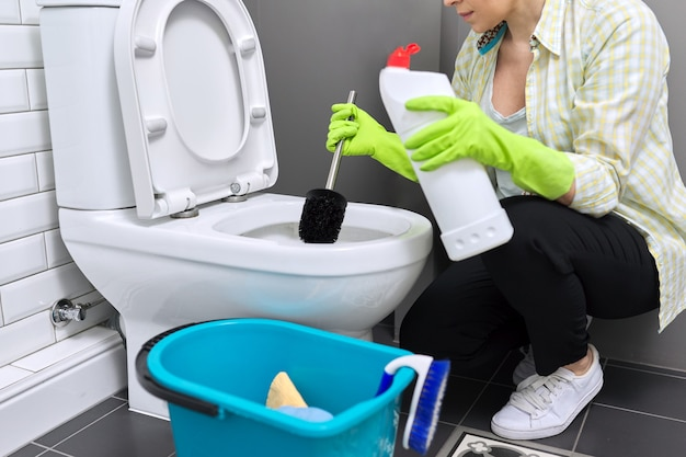 主婦がトイレを洗って消毒します。洗剤とブラシで手袋をはめた女性。ハウスキーピング、自宅の清潔さ、家事、サービス、人のコンセプト
