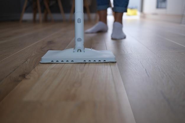 집에서 스팀 브러시로 바닥을 씻는 주부