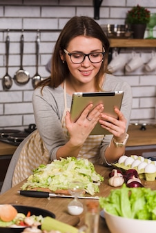 Housewife watching tablet while standing in kitchen