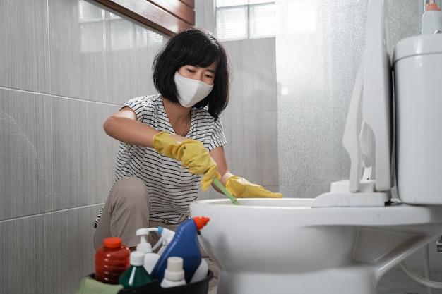화장실에서 더러운 화장실을 닦고 장갑을 끼고 마스크를 쓰고 주부