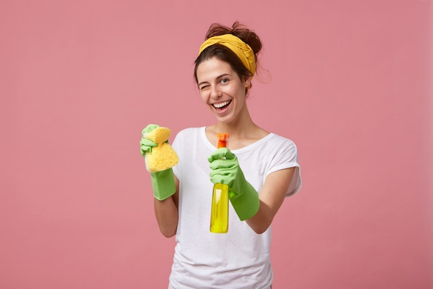 Housewife in white t-shirt and green gloves holding sponge and cleaner in hands blinking with her eyes having glad expression while washing. young pretty female doing domestic work