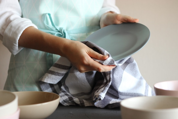 Housewife wipes the dishes with a towel