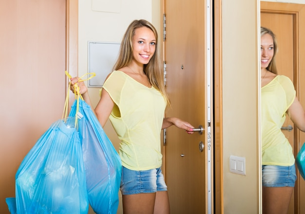 Housewife with bags of garbage indoor Premium Photo