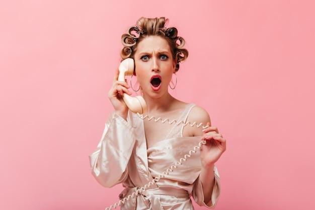 La casalinga con i capelli ricci vestita con una tunica di seta guarda indignata e scioccata davanti e parla al telefono