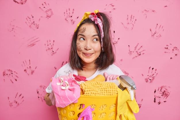 Домохозяйка с темными волосами позирует возле корзины, полной грязного белья, с грязным лицом, изолированным на розовом