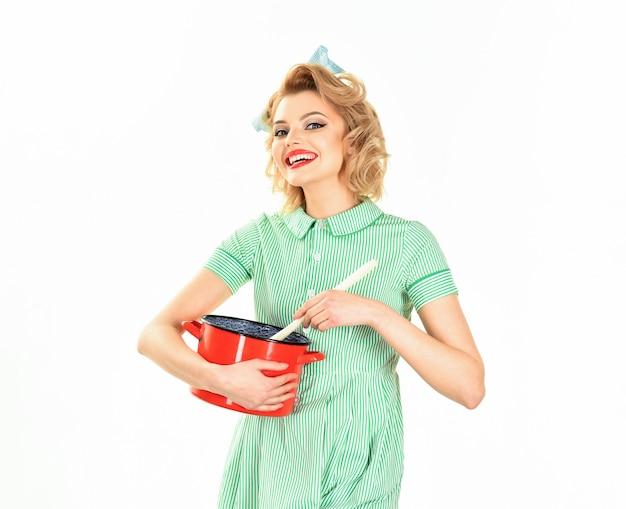 Домохозяйка с кастрюлей на белой кухне, женщина-повар держит посуду в стиле ретро горничной