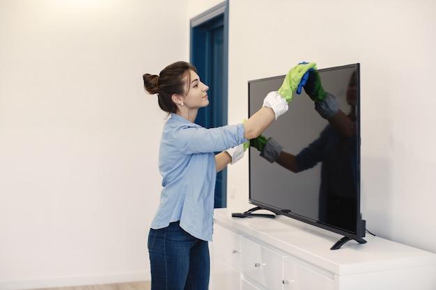 집에서 주부 워킹. 파란 셔츠에있는 여자. 여자 깨끗한 tv.