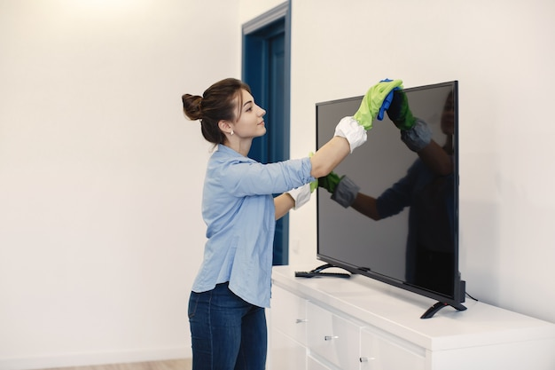 Housewife woking at home. lady in a blue shirt. woman clean tv.