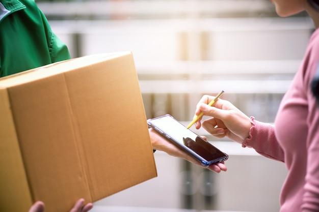 主婦女性が国境のないテクノロジーの世界に応え、デジタル時代のスマートフォンで送り主からの荷物にサイン。