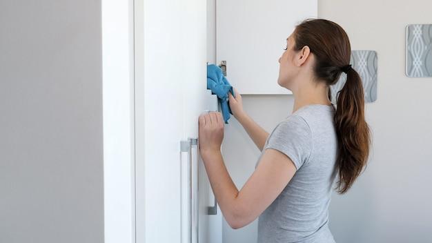 주부, 젊은 여성은 집에서 가구를 먼지, 측면 보기. 그녀는 아파트를 청소합니다.