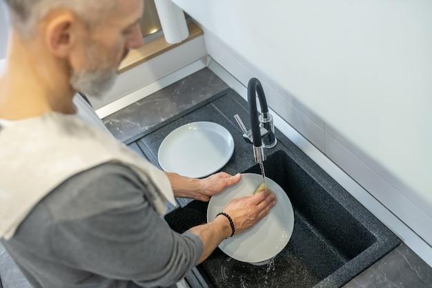 家事。台所で皿を洗っている男のクローズアップ