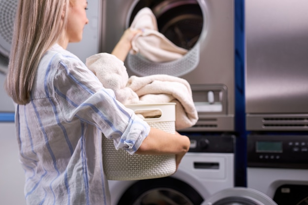 Housework: woman loading clothes into washing machine. caucasian lady enjoys cleaning process. focus on towels in basket