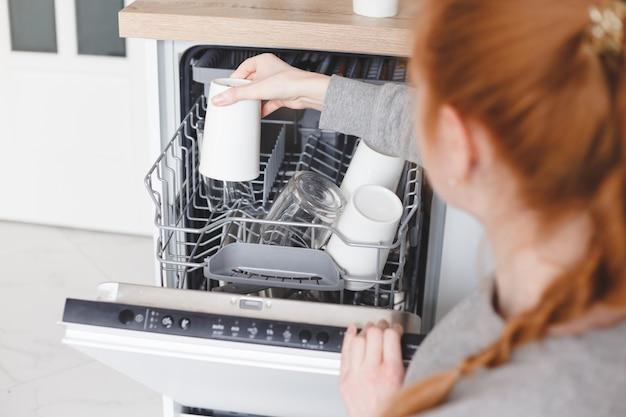 Работа по дому: молодая женщина ставит посуду в посудомоечную машину