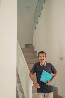 Застройщики улыбаются с сертификатами на дом, когда спускаются по лестнице в доме