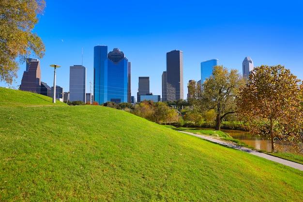 公園の芝生から晴れた日にヒューストンのスカイライン