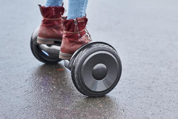 Закройте вверх женщины используя hoverboard на дороге асфальта. ноги на электрический скутер открытый
