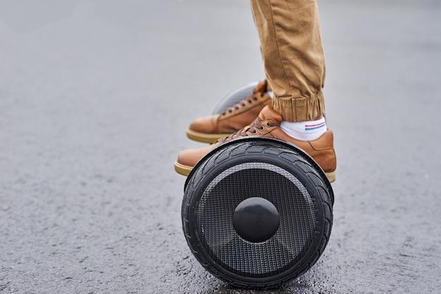 Закройте вверх человека используя hoverboard на дороге асфальта. ноги на электрический скутер открытый