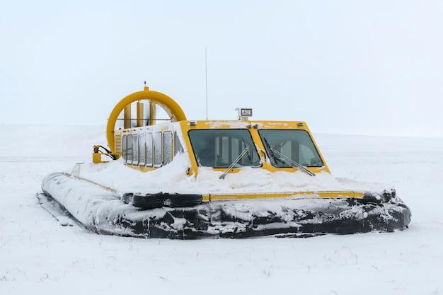 冬のツンドラのホバークラフト。ビーチのエアクッション。雪の下で黄色のホバークラフト。