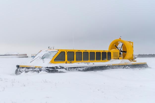 Судно на воздушной подушке в зимней тундре. воздушная подушка на пляже. желтый парящий корабль под снегом.
