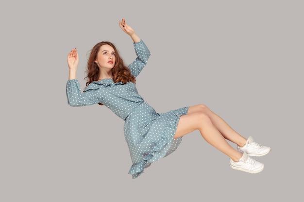 Парящая в воздухе девушка, летящая в воздухе, глядя вверх с мечтательным расслабленным выражением лица