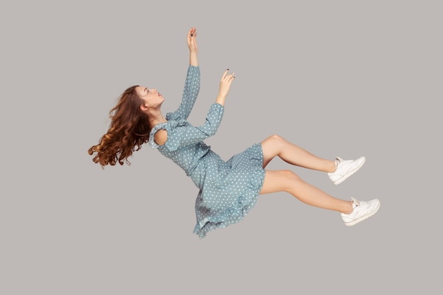 空中に浮かんでいます。リラックスした美しい女の子のフリルドレスと巻き毛の高騰する髪は、手を上げて夢の中で飛んで、何か高いものに手を伸ばします。灰色の背景で隔離の屋内スタジオショット