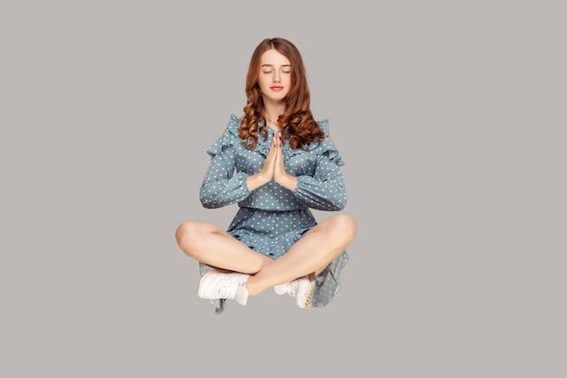 Парение в воздухе. расслабленная девушка левитирует с молитвенным жестом, медитируя сидя в позе йоги.