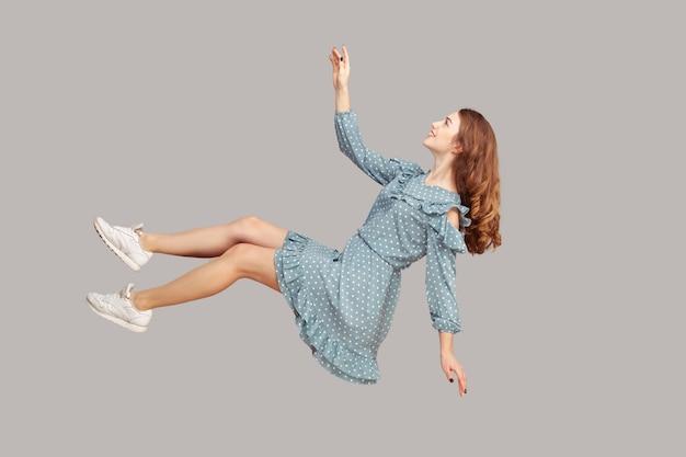 Парение в воздухе. улыбающаяся девушка, летящая в воздухе, счастливая глядя вверх и поднимая руку, чтобы поймать.