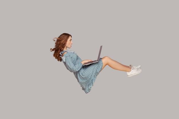 Парение в воздухе. удивленная девушка в платье с рюшами левитирует, потрясенно глядя на экран ноутбука