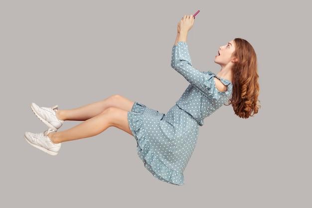 Парение в воздухе. удивленная шокированная девушка в платье с рюшами левитирует с мобильным телефоном