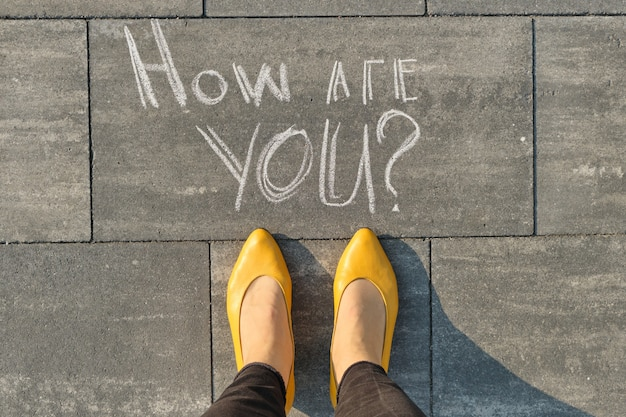 How are you written on gray sidewalk with women legs.
